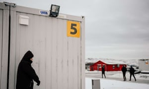A refugee smokes a cigarette outside the sleeping facilities at the arrival centre for refugees near the town on Kirkenes in northern Norway.