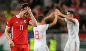 Hungary players celebrate their win behind a dejected Gareth Bale