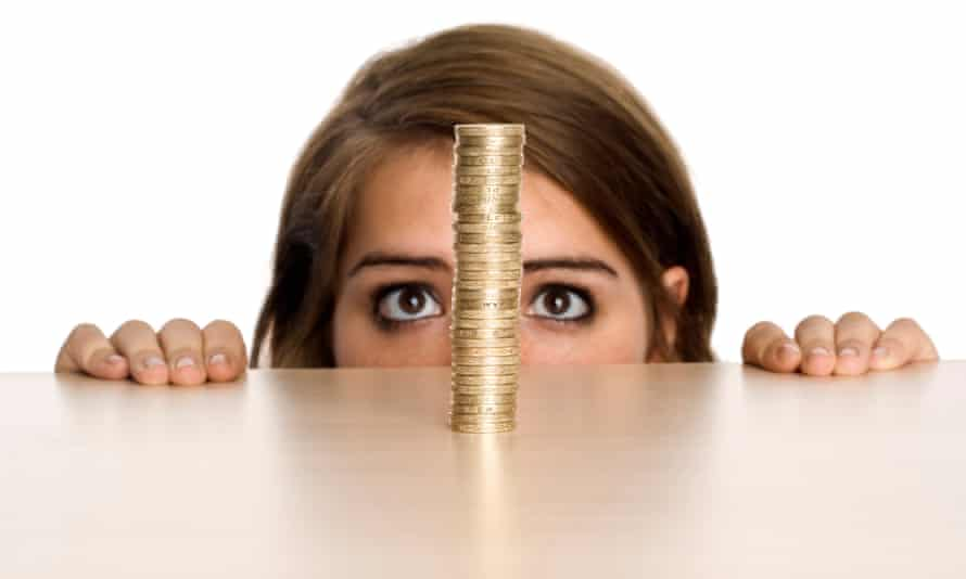 A teenage girl watching a stack of Pound coins