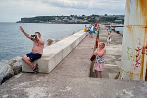 A wife looks at her husband as he waves out to a passing boat through his binoculars at Brixham harbour.
