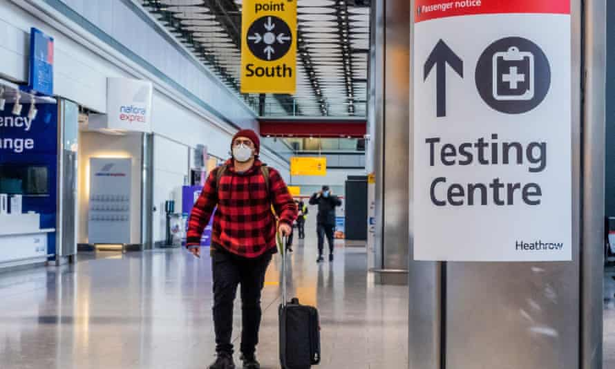 a masked man passes through Heathrow next to Covid testing signs