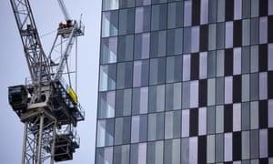 a crane besides an office block