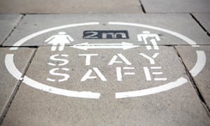 A 'Stay Safe 2 metres' sign on the pavement in Oldham town centre in Greater Manchester