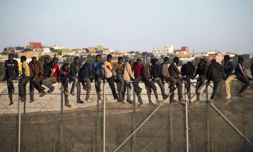 People sit on a border fence separating Melilla from Morocco