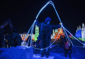 A laborer arranges lights to be placed in large ice blocks