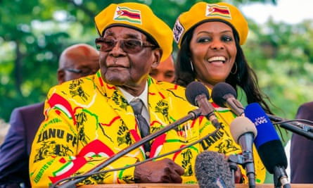 Robert Mugabe (left) addresses party members and officials at his party headquarters to show support to his wife Grace (right).