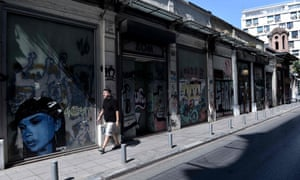 A man walks past closed shops in Thessaloniki.