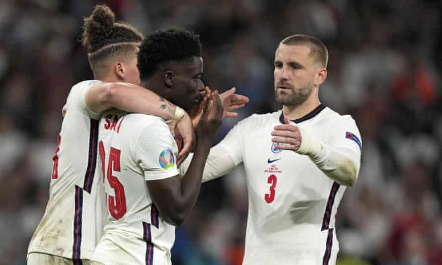 Bukayo Saka (centre) is comforted after failing to score a penalty against Italy