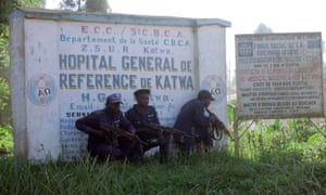 Police guards shelter behind a hospital sign in Butembo the day after an Ebola treatment centre in the city's Katwa district was attacked by militia