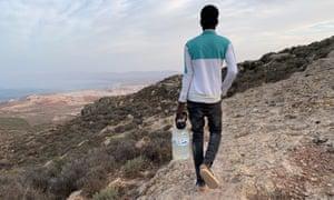Pengungsi Mali berusia 18 tahun membawa botol air isi ulang di mata air, berjalan kembali ke kamp migran di Gunung Gurugu, Maroko, 25 September 2020.