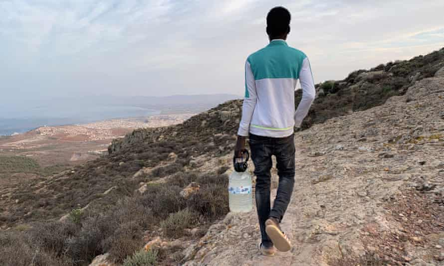 18-year old Malian refugee carrying a water bottle refilled in a spring, walks back to a migrant camp in Gurugu Mountain, Morocco, 25 September 2020.