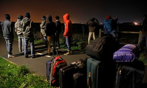 People at the now defunct refugee camp in Calais known as 'the Jungle' wait to be seen by the French authorities