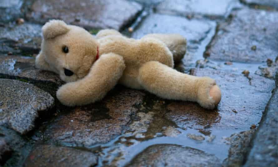Abandoned teddy bear in wet gutter