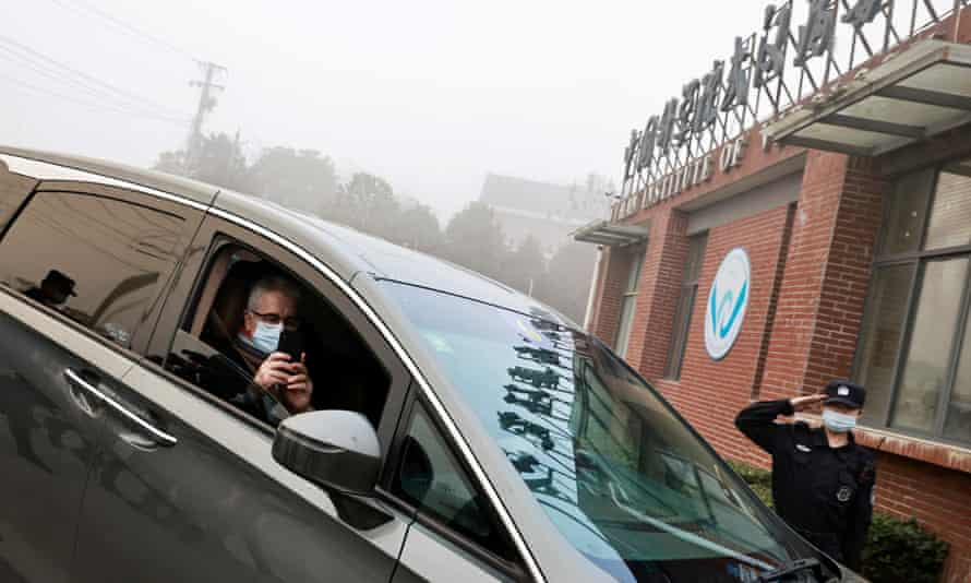 man in a car outside orange brick building against smoggy sky