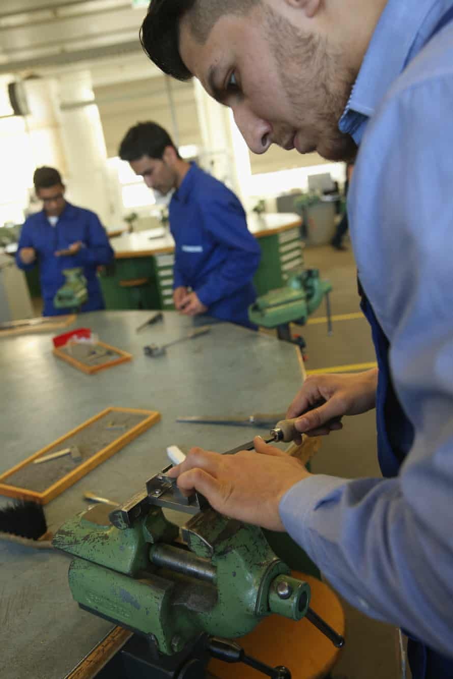 Participants in a job-training scheme for refugees work with metal at a Siemens centre in Berlin.