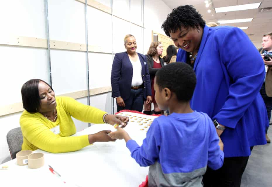 Abrams watches as her nephew receives a sticker after she voted early at the South DeKalb Mall in Decatur, Georgia.