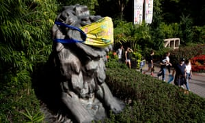 People exit the Smithsonian National Zoological Park beside a statue of a lion that is decorated with a face mask in Washington, DC, USA.Six lions and three tigers at the National Zoo have tested positive for Covid-19 and are receiving treatment, the zoo said.