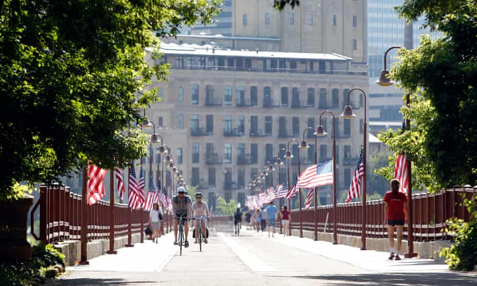 Cyclists and walkers cross the pedestrian-only stone arch bridge that crosses the Mississippi River in Minneapolis.