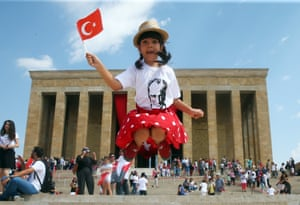 A girl jumps and waves her flag at Ataturk's mausoleum, Anitkabir, during the celebrations marking the 95th anniversary of Turkey's Victory Day