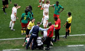 Referee Qin Liang approaches Phil Neville (bottom left) and Cameroon head coach Alain Djeumfa.