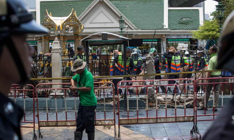 Policemen stand guard in front of the Erawan Shrine following the blast.