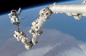 Astronaut Stephen Robinson attached to a robotic arm in space