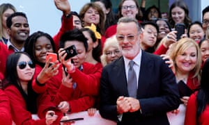 Hanks, bearded, wearing glasses, clutching hands together,  in front of crowd of well-wishers all dressed in red