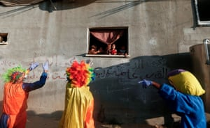 Clowns entertain Palestinian children during a lockdown imposed by the local authorities following a surge in coronavirus cases in Khan Younis.