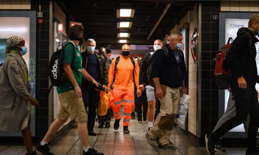Commuters wear face masks as they pass through Vauxhall underground station
