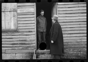 One man stands in a doorway; a second man, in a hat and overcoat, stands outside the door looking at him