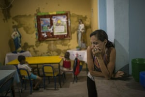 A volunteer waits for children to arrive for lunch in the San Antonio de Padua dining room in the slum of Petare.