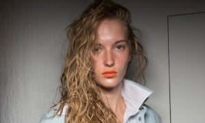 A model with long, wavy red-orange hair, and orange lips and facial glow