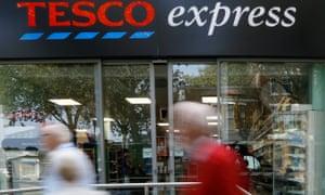 Pedestrians pass a Tesco shop