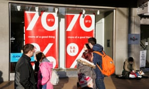 Shoppers pass a 70% reduction sign in a shop window