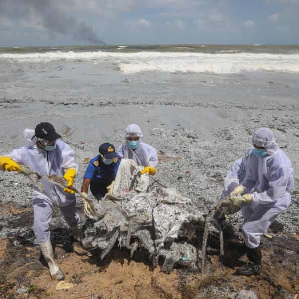 Sri Lanka navy personnel clear debris from the X-Press Pearl, which had 25 tonnes of nitric acid and other chemicals onboard.