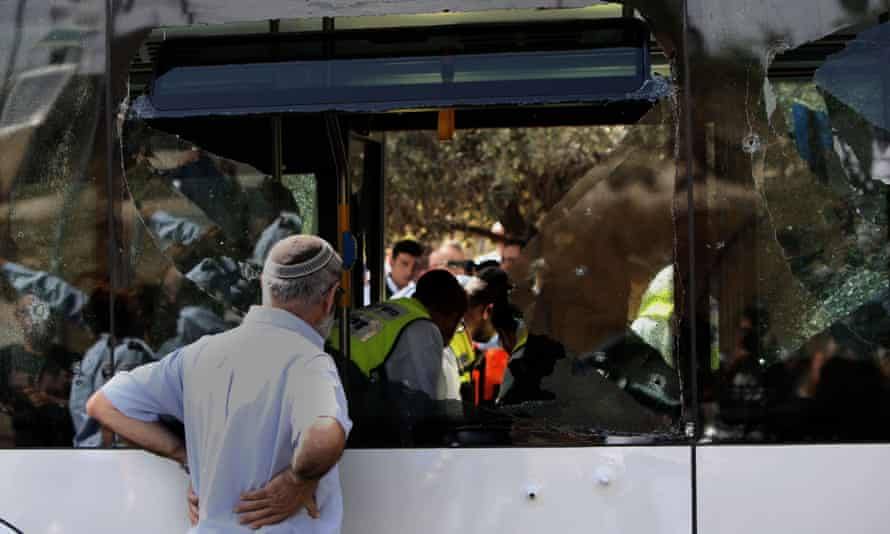 Volunteers and security forces inspect the scene following an attack on a bus in east Jerusalem