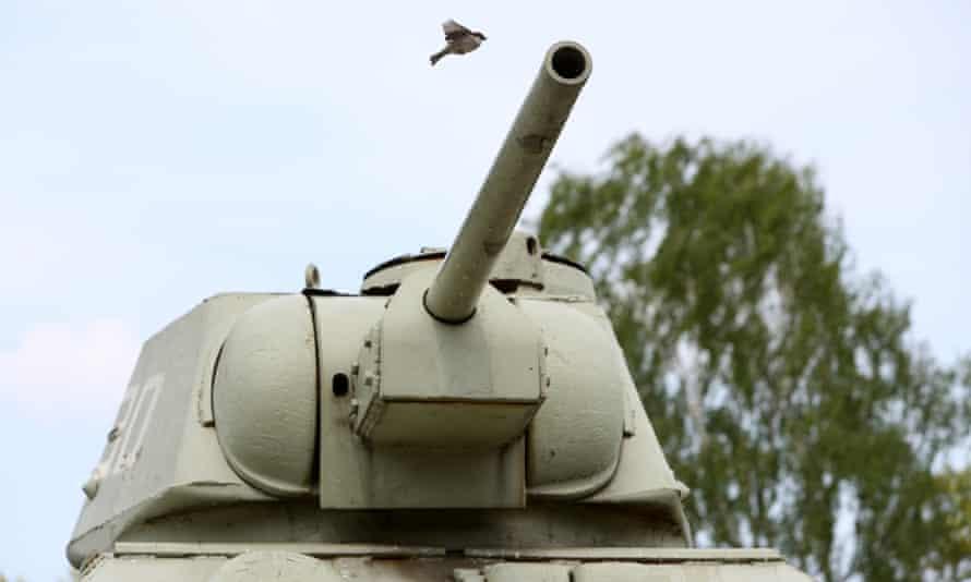 A bird flies over of one of two Soviet T-34 tanks in a Soviet war memorial in the Tiergarten in Berlin.