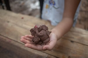 A clay statue made by a child is brought for immersion at August Kranti Maidan's artificial ponds.