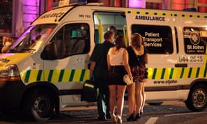 People talk to a friend being treated in an ambulance parked outside a night spot in Cardiff city centre.