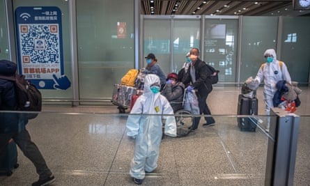 Coronavirus outbreak: passengers wearing protective masks and suits arrive at Beijing airport.