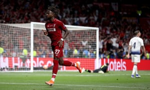 Divock Origi celebrates after scoring Liverpool's second goal to secure the trophy.
