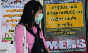 A Thai woman in a protective mask walks past signs giving information on Mers virus in Thailand. The country confirmed its first case just as an outbreak in South Korea appears to have peaked.