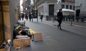 A homeless man sleeps on Wall Street near the New York Stock Exchange.