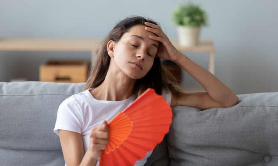 teenage girl cooling herself with a fan