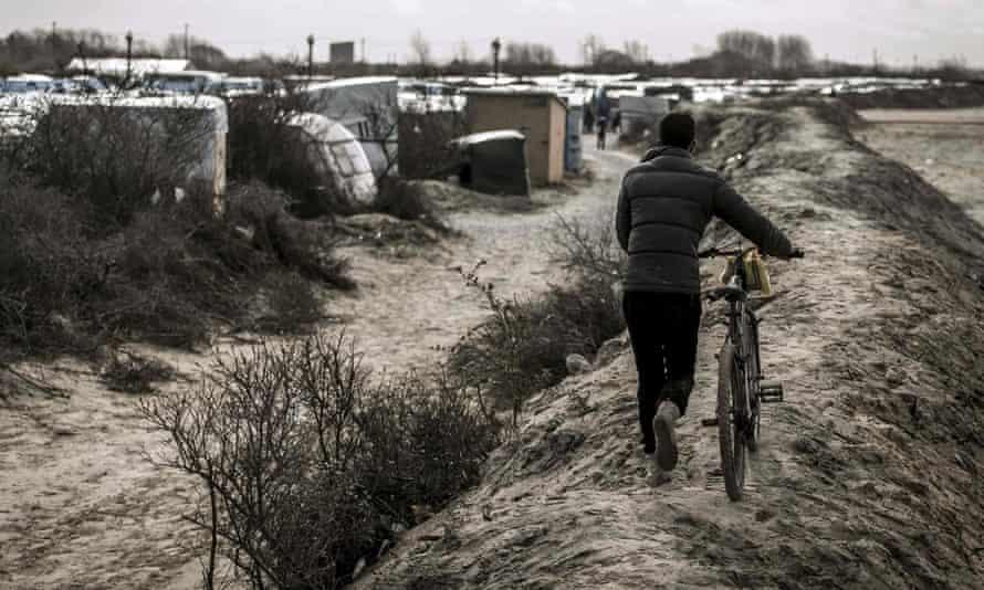 A refugee pushes his bike