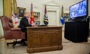 Donald Trump makes a video call to members from the army, marines, navy, air force, and coast guard stationed worldwide from the Oval Office on Christmas Day.