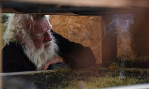 Bruce Pascoe looks into the harvest hopper at the burning chaff from seed