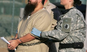 A shackled detainee is transported by a female guard, front, and male guard, behind, away from his annual administrative review board hearing at Guantánamo Bay on 6 December 2006.