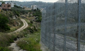 A barbed-wire fence at the edge of the Palestinian village of Al Walaja in the West Bank