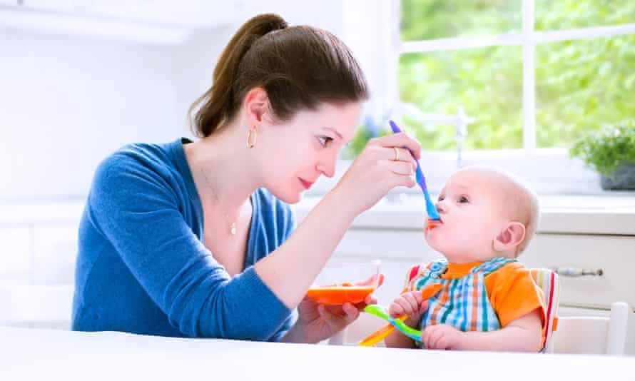 A mother feeding her baby solids
